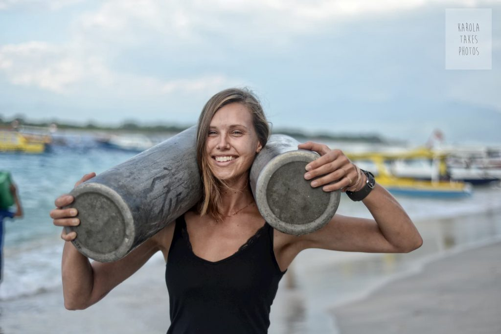 Divemaster Nicole with tanks looking strong